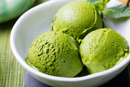 Photo for Green tea matcha ice cream scoop in white bowl on a wooden background Close up. - Royalty Free Image