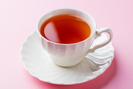 Foto de Tea in white cup on pink background. Close up - Imagen libre de derechos