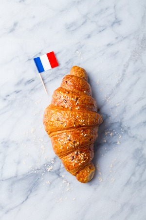 Photo for Fresh croissant with French flag on marble table background. Top view. Copy space. - Royalty Free Image