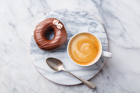 Foto de Coffee in a white cup with chcolate donut on marble board. Top view - Imagen libre de derechos