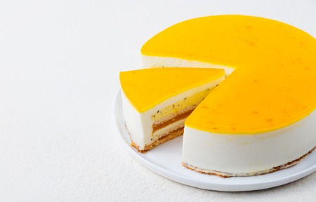 Photo for Passion fruit cake, mousse dessert on a white plate. Copy space - Royalty Free Image