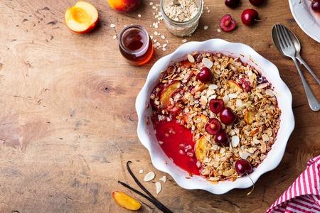 Foto de Peach and berry crumble in a baking dish. Top view. Copy space - Imagen libre de derechos
