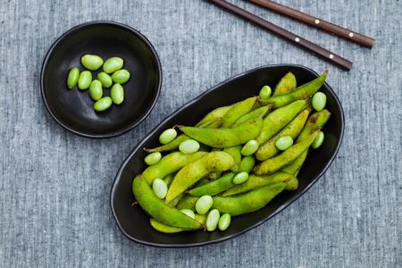 Photo pour Fresh edamame green beans in black bowl. Grey background. Top view. Copy space. - image libre de droit