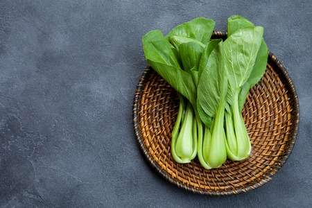 Photo pour Bok choy fresh salad on wooden plate. Grey background. Top view. Copy space. - image libre de droit