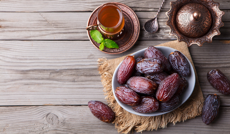 Photo for Fresh Medjool Dates in a bowl with tea - Royalty Free Image