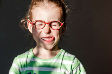 Photo pour Funny girl in red glasses frowns from the sunlight - image libre de droit