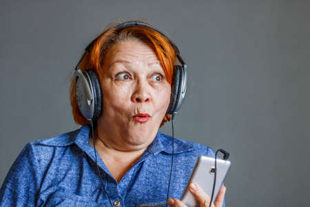 Photo for Listening to audiobooks from your phone. Elderly woman in headphones - Royalty Free Image