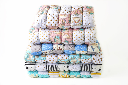 Foto de Patchwork and fashion concept - beautiful stack of colorful quilts, bedspreads stacked in several rows in height for storage, sale of stitched products on a white background - Imagen libre de derechos