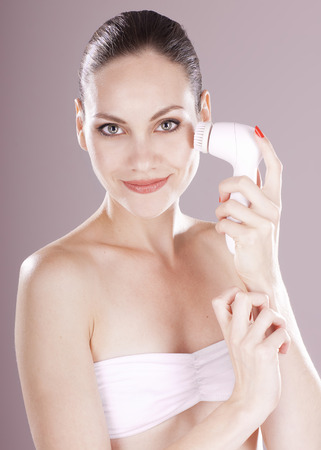 Charming woman with brush for deep cleansing facial. Skin care concept. High technology beauty.