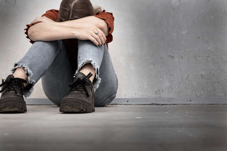 Foto de Young woman cries and sitting near a empty wall, lonely sad and depressed girl holding her head down - Imagen libre de derechos