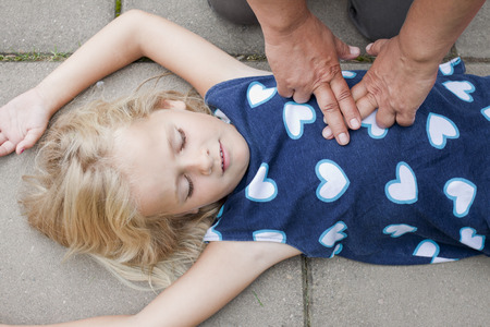 Foto de A little girl receiving first aid heart massage by nurse or doctor or paramedic - Imagen libre de derechos