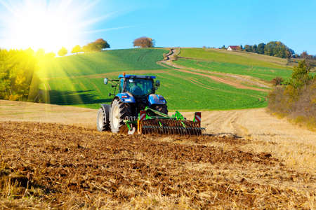 Photo pour Tractor plows a field in the spring, with sunlight - image libre de droit