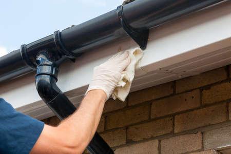 Foto de Property Maintenance - Man cleaning eaves or gutters with a cloth - Imagen libre de derechos