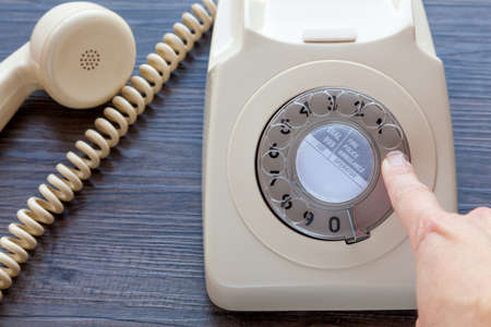 Foto de Person making a telephone call using an old fashioned telephone - dialing a number - Imagen libre de derechos