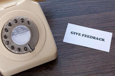 Foto de Retro telephone with note - Give Feedback - Imagen libre de derechos