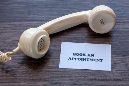 Foto de Classic telephone receiver with note - Book An Appointment - Imagen libre de derechos