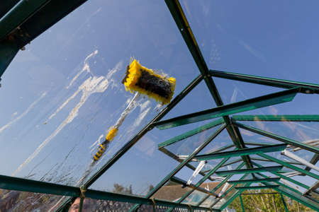Photo pour Cleaing a dirty greenhouse roof with a telescopic water fed pole - image libre de droit