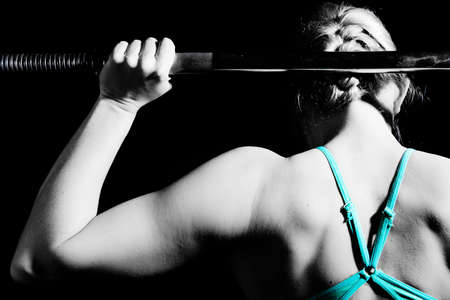 Foto de Young athletic woman pumping up muscles with barbell. black and white - Imagen libre de derechos
