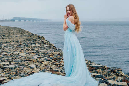 Photo for Beautiful young girl in a long blue lush dress is standing on the beach - Royalty Free Image