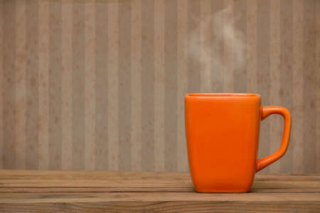 Orange mug on a wooden table over grunge wallpaper. Steaming coffee or tea cup