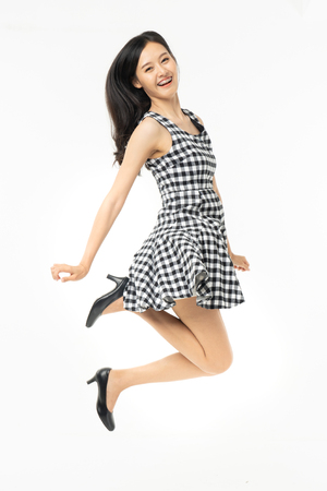 Foto de portrait of excited surprised attractive careless inspired girl jumping up isolated on background.Freedom legs stylish feet glamorous people teenager asian. - Imagen libre de derechos