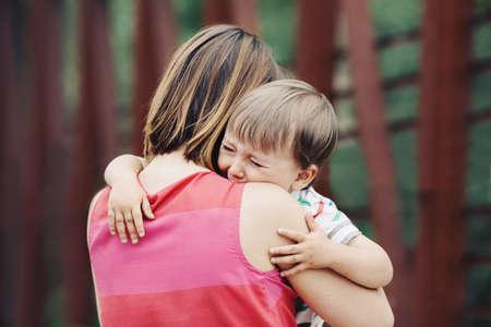 Foto de Portrait of  young Caucasian woman mother comforting her crying little toddler boy son outside in park on summer day, parenthood lifestyle concept - Imagen libre de derechos
