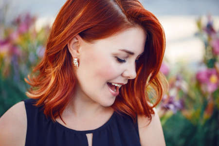 Foto de Closeup portrait of smiling laughing flirty middle aged white caucasian woman with waved curly red hair in black dress screaming outside in park - Imagen libre de derechos