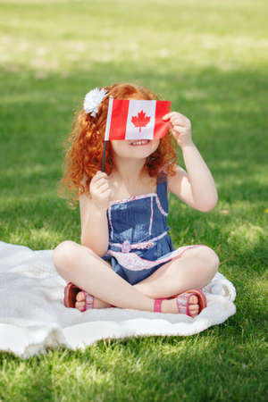 Foto de Portrait of  cute little red-haired Caucasian girl child holding Canadian flag with red maple leaf, sitting on grass in park outside, celebrating Canada Day anniversary - Imagen libre de derechos