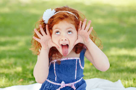 Photo pour Portrait of cute adorable little red-haired Caucasian girl child in blue dress making funny silly faces showing tongue, in park outside, playing  crying screaming, having fun, lifestyle childhood - image libre de droit