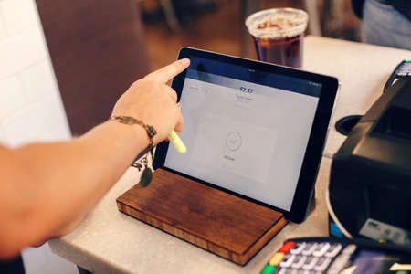 Photo for Closeup shot of young caucasian female woman cashier hands. Seller using touch pad for accepting client customer payment. Small business of coffee shop cafeteria. - Royalty Free Image