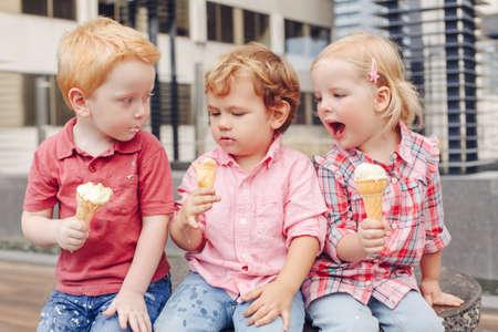 Foto de Group portrait of three white Caucasian cute adorable funny children toddlers sitting together sharing ice-cream food. Love friendship fun concept. Best friends forever. - Imagen libre de derechos