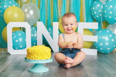 Foto de Portrait of cute adorable Caucasian baby boy in jeans pants celebrating his first birthday. Cake smash concept. Child kid sitting on floor in studio eating tasty yellow dessert  - Imagen libre de derechos