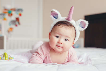 Photo pour Portrait of cute adorable Asian mixed race smiling baby girl four months old lying on tummy on bed in bedroom wearing unicorn headband horn and ears looking in camera. - image libre de droit