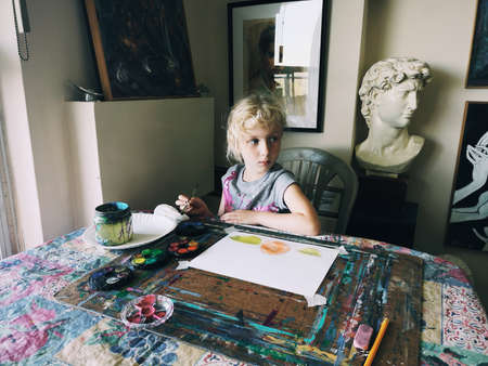 Photo pour Toronto, Ontario, Canada - June 3, 2019: Caucasian preschooler girl sitting in art studio concentrated on painting fruits with brushes and water color paints. Children hobby activity. - image libre de droit