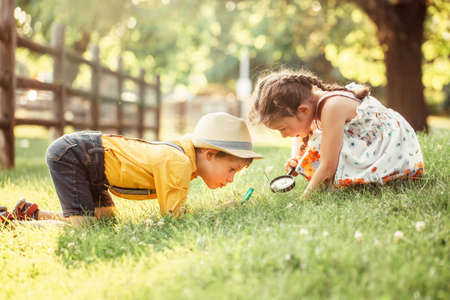 Photo for Cute adorable Caucasian girl and boy looking at plants grass in park through magnifying glass. Children friends siblings with loupe studying learning nature outside. Child education concept. - Royalty Free Image