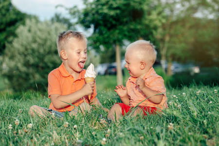 Foto de Two Caucasian funny children boys siblings sitting together eating sharing one ice-cream. Toddler younger baby crying and older brother teasing him. Love envy jealous brothers friendship. - Imagen libre de derechos