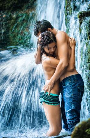 Photo pour Couple hugging and kissing under waterfall - image libre de droit