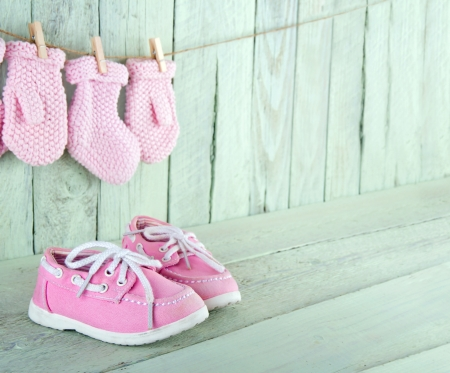 Photo for Pink toddler shoes on wooden light green vintage background with copy space - Royalty Free Image