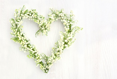Photo pour Heart shaped flower wreath of lilys of valley on white wooden background - image libre de droit