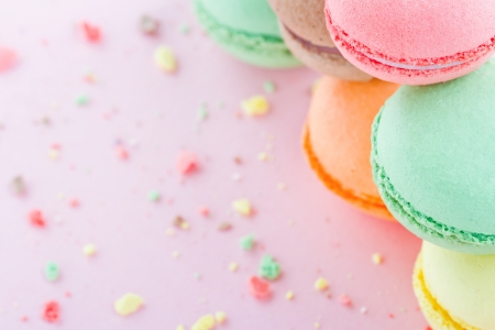 Photo for Pile of colorful macaroons on pastel pink background with small crumbs - Royalty Free Image