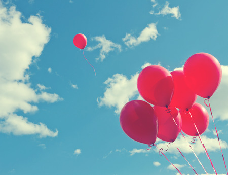 Foto de Bunch of red ballons on a blue sky with one balloon escaping to be individual and free - concept for following one's dreams - Imagen libre de derechos