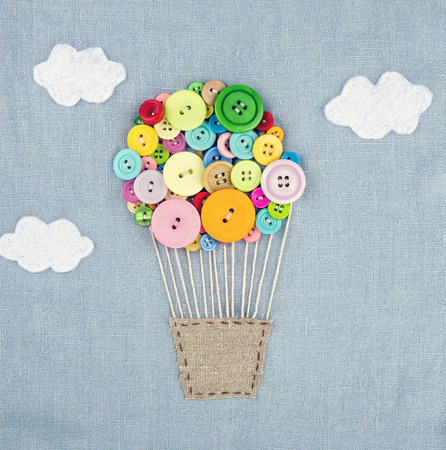 Photo for Handmade crafts of hot air balloon made of multicolored buttons on light blue linen textile background - Royalty Free Image
