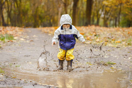 Photo pour Happy two years old boy jumping on muddy puddles in rubber boots - image libre de droit