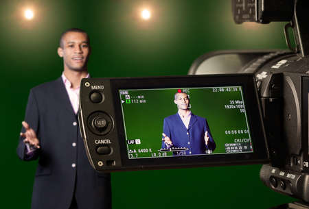 Foto de Television presenter in a green screen TV studio, seen through the LCD display of a digital camera. Selective focus on the viewfinder. - Imagen libre de derechos