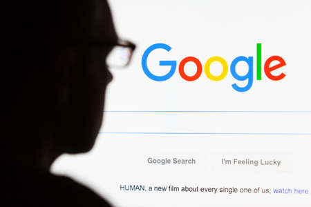 Photo for BATH, UK - SEPTEMBER 12, 2015: Close-up of the Google.com search homepage displayed on a LCD computer screen with the silhouette of a man's head out of focus in the foreground. - Royalty Free Image