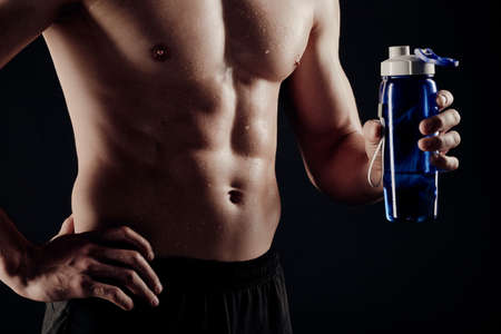 Foto per Muscular man shows his body off at the camera with a water bottle. - Immagine Royalty Free