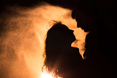 Photo for Loving couple silhouette. The wind carries sand. - Royalty Free Image
