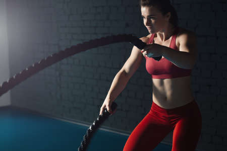 Photo for Woman make exercise with battle rope in functional training gym - Royalty Free Image