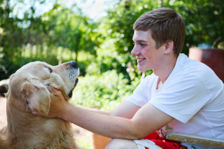 Happy young teenager with golden retriver dog together embracing