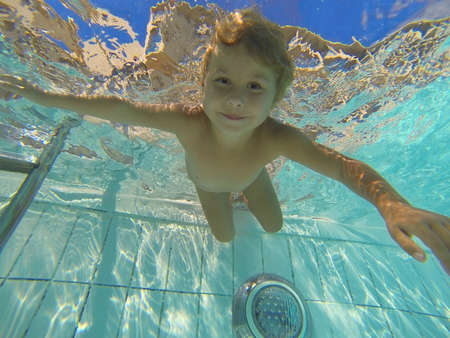 Little child swimming under water in pool